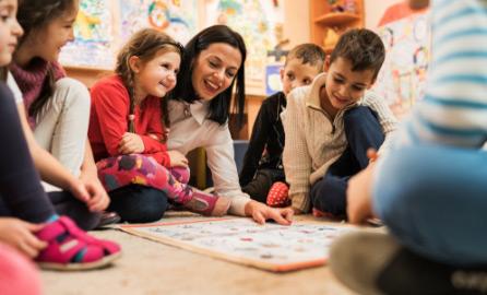 Auf dem Bild ist eine Kindergartengruppe, auf dem Boden spielend zu sehen.