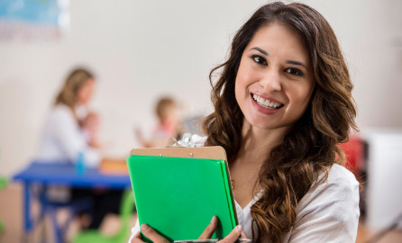 Auf dem Bild ist eine fröhliche Jugendliche zusehen, die eine Schulmappe im Arm hat.