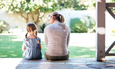 Auf dem Bild ist eine Frau mit einem kleinen Kind zu sehen. Aufgenommen sitzend von hinten Fotografiert auf einer Veranda.