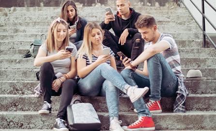 Auf dem Bild ist eine Gruppe Jugendlicher auf einer Treppe sitzend zu sehen mit Smartphone in der Hand.